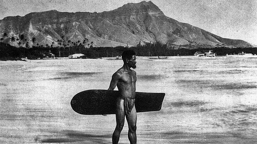 The lone Hawaiian surfer wearing the malo at Waikiki Beach carries one of the last Alaia surf board. The surfer was Charles Kauha. Frank Davey photographed Charles Kauha in 1898 in numerous poses, but none are of Kauha surfing.